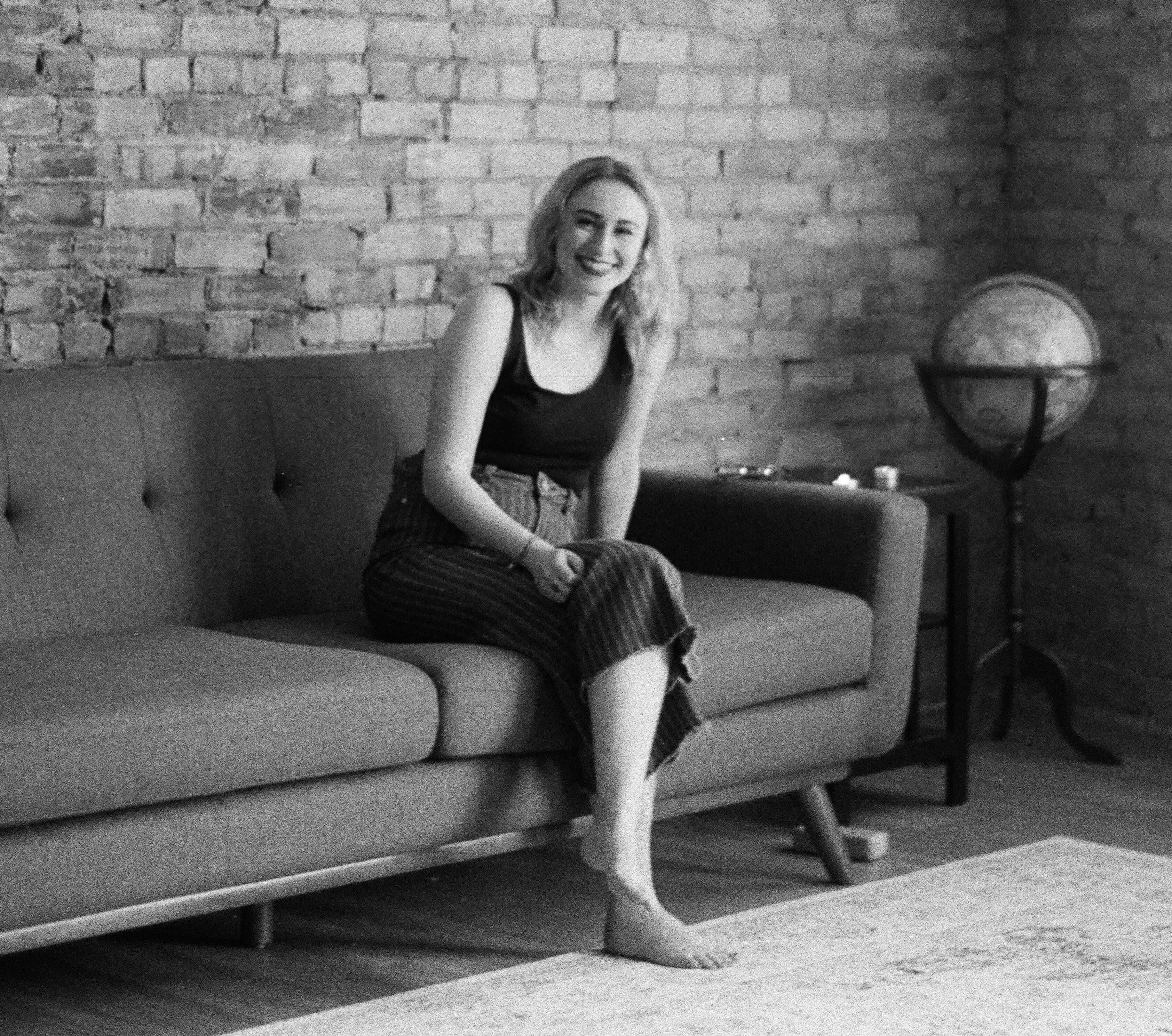 black-and-white photo of tess, sitting cross-legged on a couch, smiling into the camera